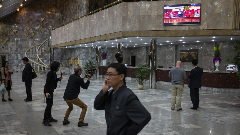 Transeúntes miran por televisión el discurso de Kim Jong-un en la Inaugu...
