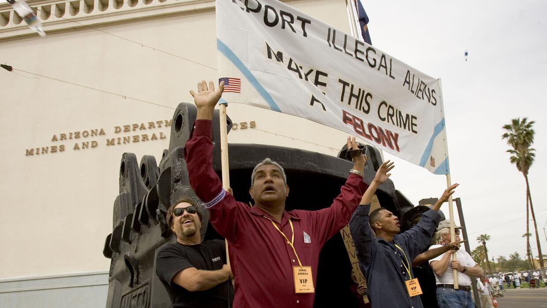 Dos activistas proinmigración protegen a un grupo de contramanifestantes...