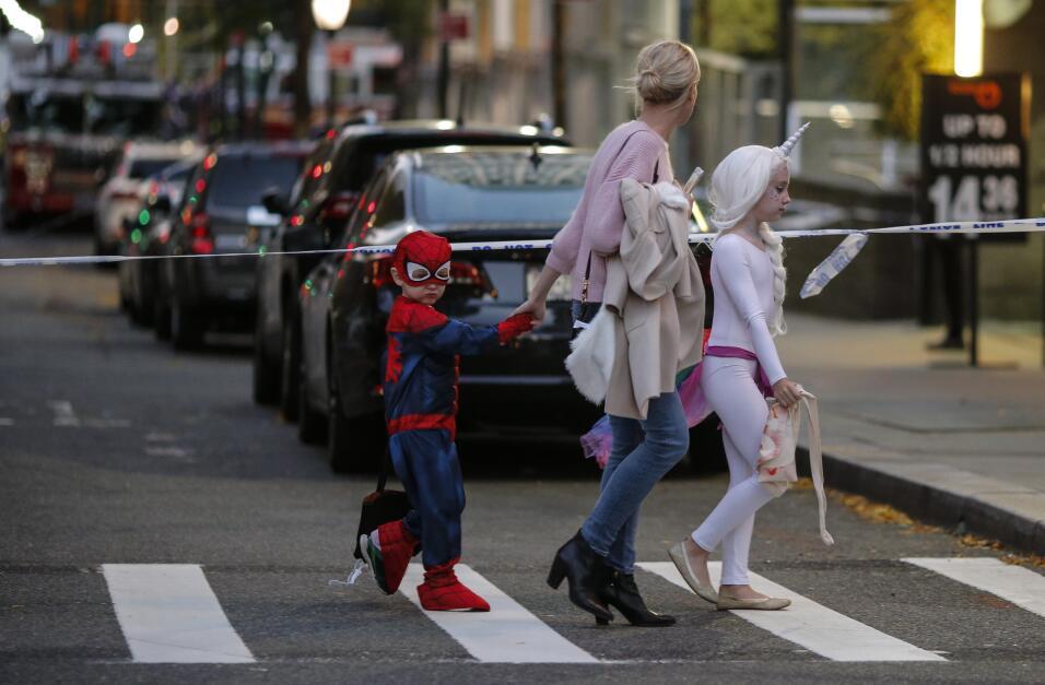 Unos niños disfrazados para la celebración de Halloween caminan cerca de...