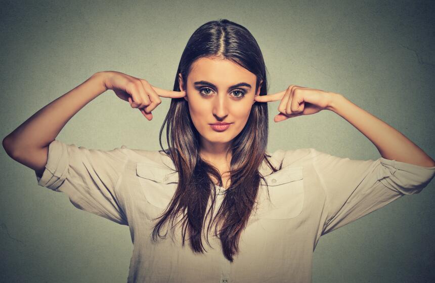 Mujer tapándose los oídos