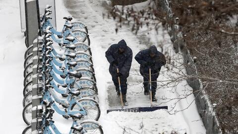 Dos empleados limpian una acera en Chicago este viernes 9 de febrero.