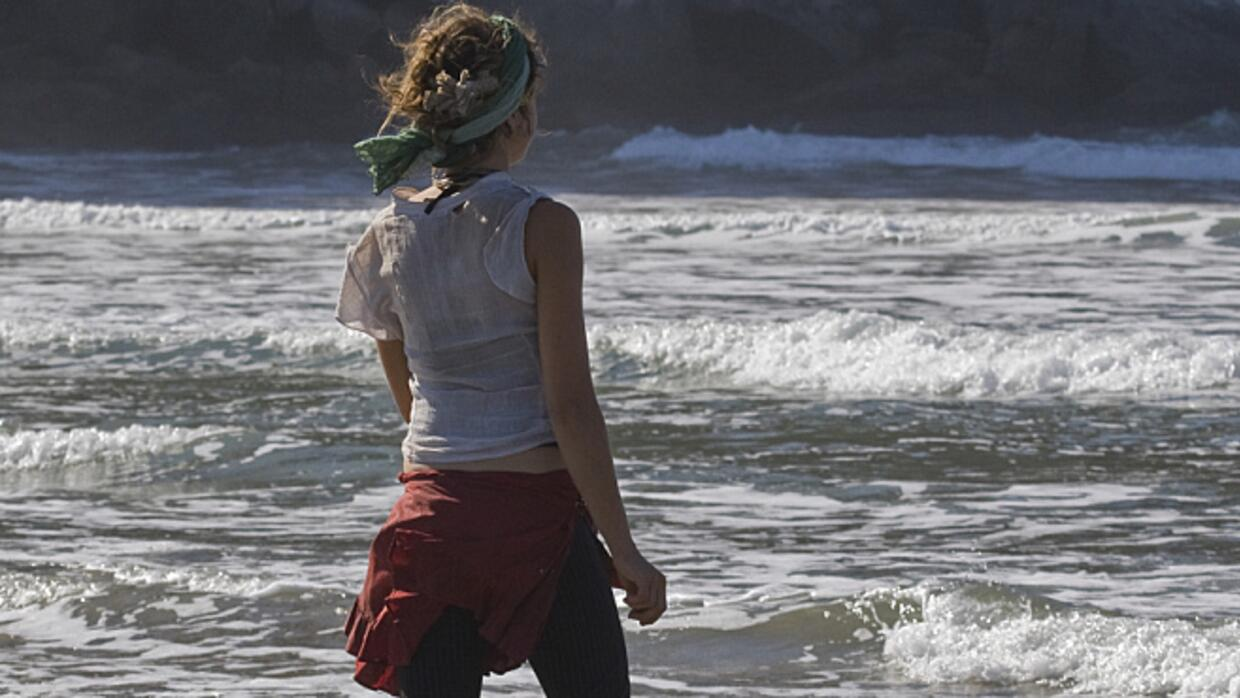 A teenage girl looking out at the ocean.