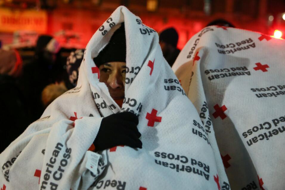 Los evacuados usan mantas mientras se paran después de un incendi...