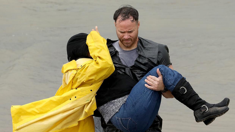 Un voluntario carga a una damnificada luego del paso del huracán Harvey,...