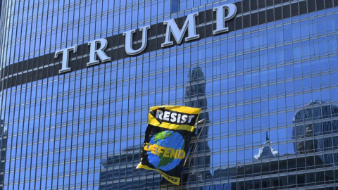 Manifestantes guindaron una bandera gigante para protestar la salida de...