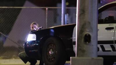 Una agente de la policía de Las Vegas se protege detrás de una partrulla...