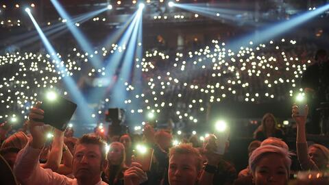 Asistentes a un concierto por la paz, en Túnez, usan sus celulare...