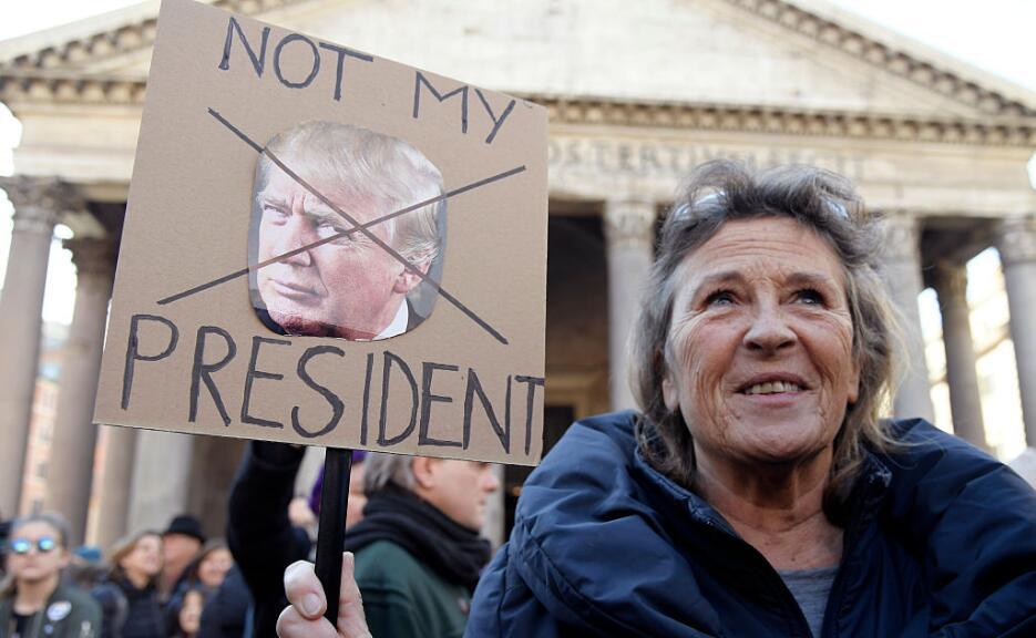 En Roma, Italia, esta mujer sostiene un cartel contra el presidente de E...