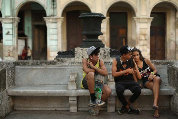 Tres adolescentes ven pasear a los turistas a lo largo del famoso Paseo...