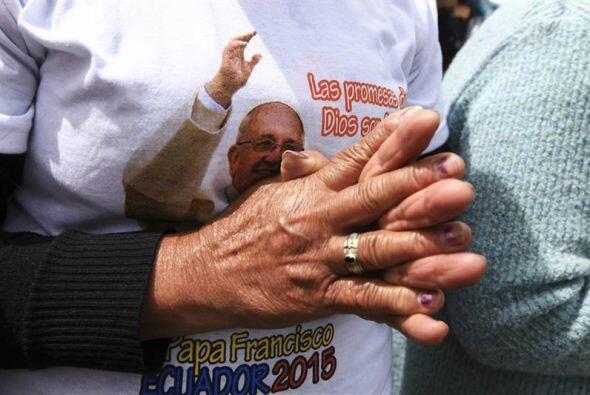 Esta mujer con una camiseta con Papa, mantiene unidas sus manos durante...