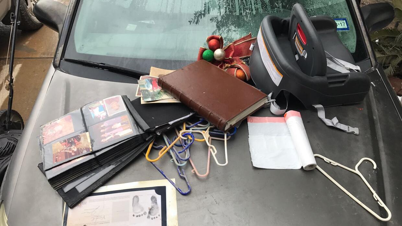 Un álbum de fotos familiar y otras pertenencias se secan sobre un carro...