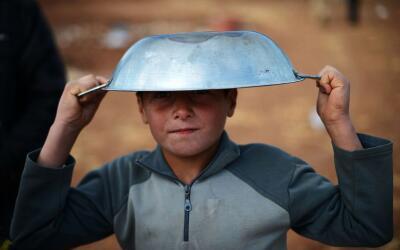 Un pequeño desplazado sirio sostiene una cazuela vacía mie...