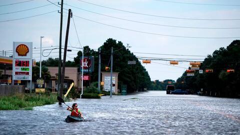 Una mujer navega por una calle inundada en Houston, Texas, despué...