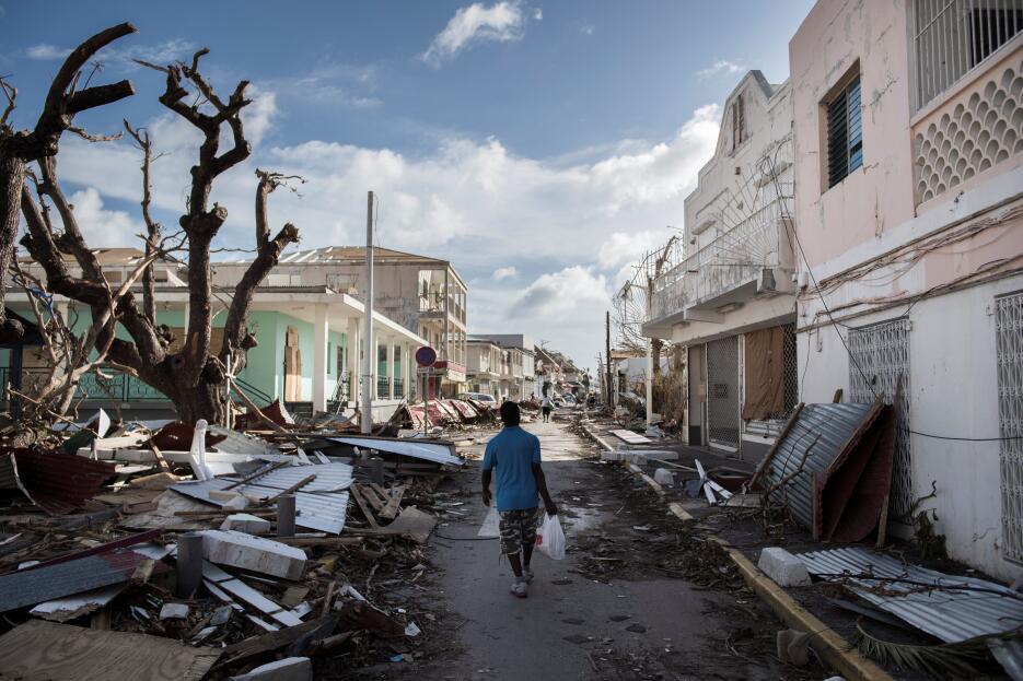 Un hombre camina por una calle cubierta de escombros tras el paso del hu...