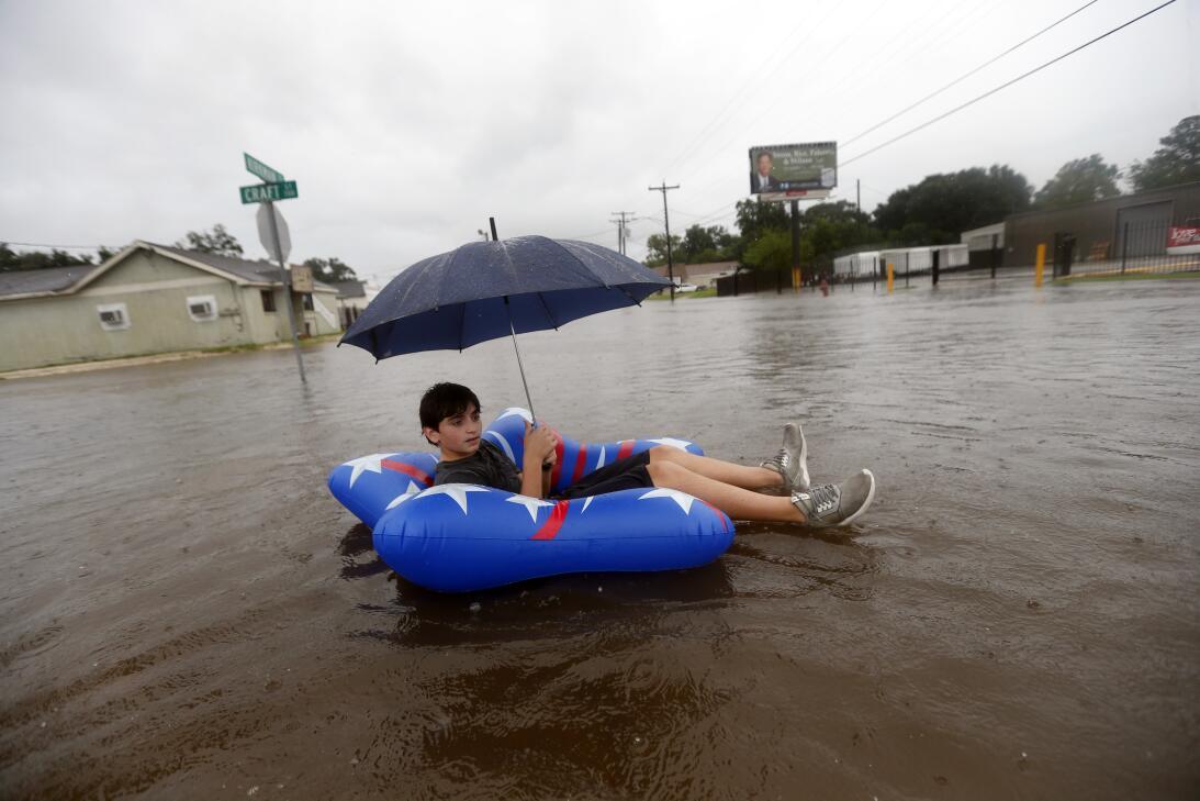 Julius Verret, de 14 años, flota en las inundaciones de la calle en Lake...