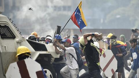 Protesters in Caracas attack a National Guard armored vehicle.