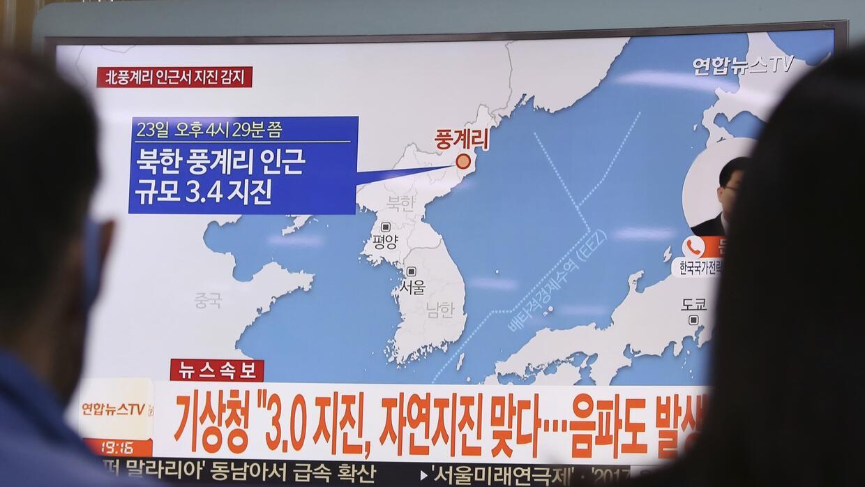 Gente mirando un reporte noticioso en televisión sobre un sismo en Corea...