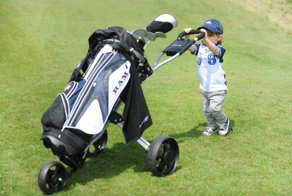 Él es mucho más bajo que el carrito de los palos de golf, pero aún así e...