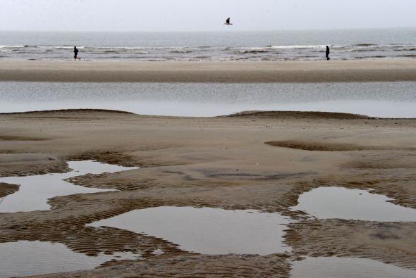 Dos hombres caminan por la playa del Mar del Norte de San Pedro- Ording,...