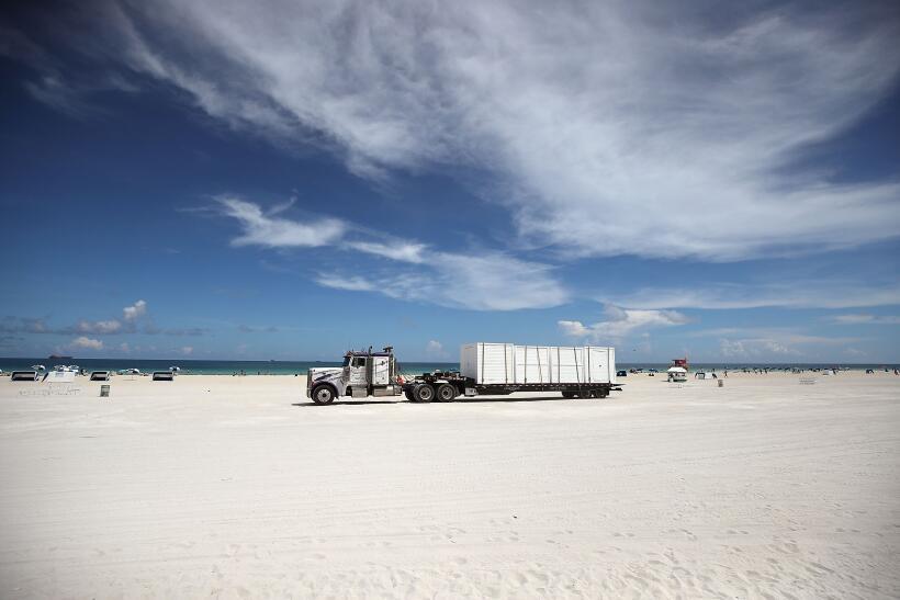 Un camión de carga se lleva las sillas de playa de Miami Beach, uno de l...