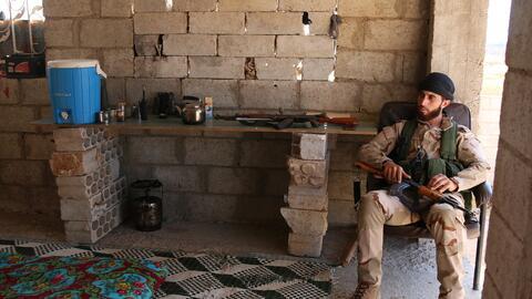 Un recluta del Free Syrian Army sentado en una silla mientras descansa e...