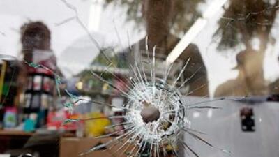 Un ventanal roto por el impacto de una bala disparada desde el automóvil...