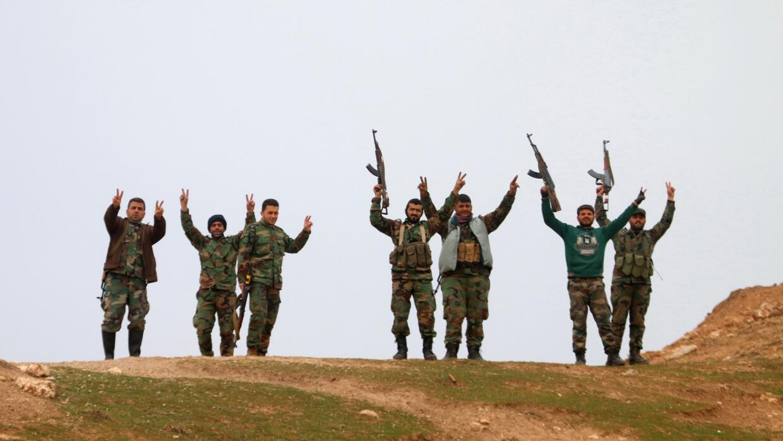 Fuerzas del gobierno sirio levantan sus armas.