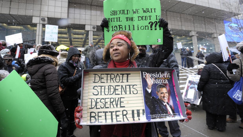Una maestra protesta durante la visita del presidente Obama a Detroit