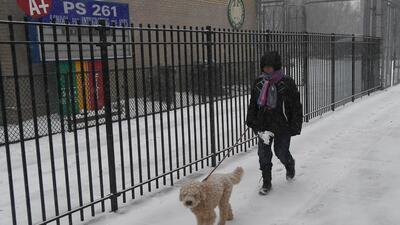 Una mujer pasea frente a una escuela cerrada por el ciclón invernal en B...