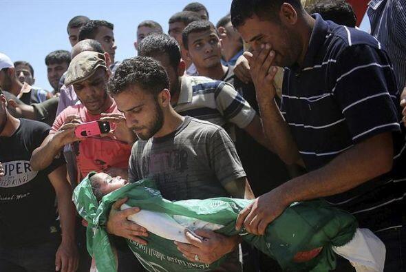 Caras largas y lágrimas durante su funeral en el campo de refugiados de...