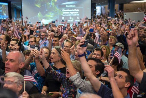 Miembros del equipo de la NASA, con banderas en mano de Estados Unidos,...