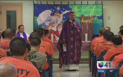 Reos de la prisión reciben bendición durante una misa navideña