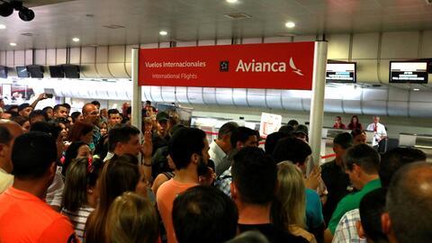 Los pasajeros de Avianca se agolpan en el mostrador de la aerolín...