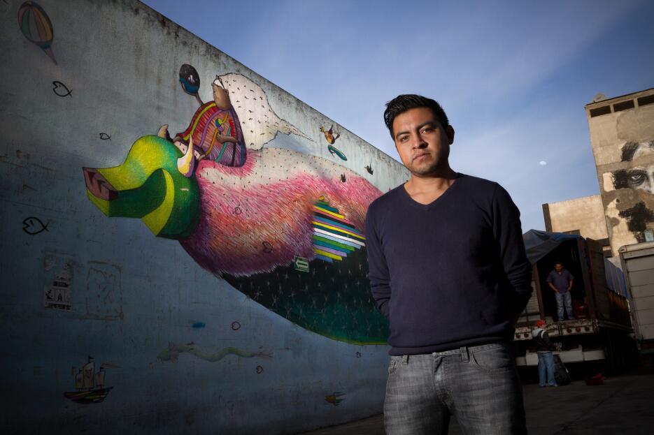 Spaik en frente de su mural.