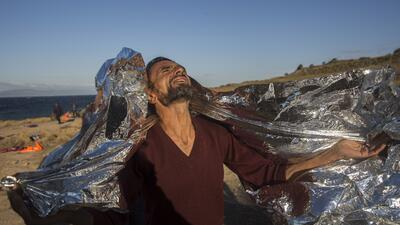 Un hombre se cubre con una manta térmica tras una travesía marítica, con...