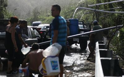 Personas sin servicio de acueductos recogen agua por una tubería...