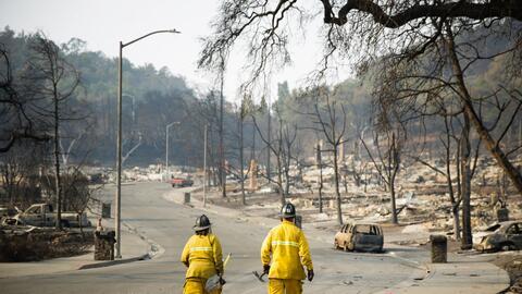 Dos bomberos caminan por el barrio de Fountaingrove en Santa Rosa, Calif...