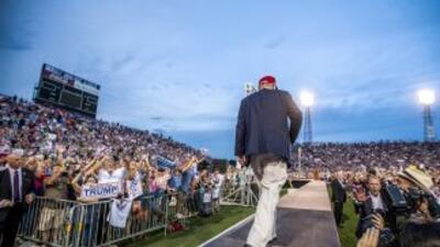 Donald Trump sube al escenario en un estadio de fútbol americano en Alab...
