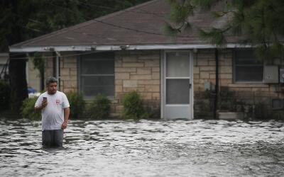 Un hombre con el agua hasta las rodillas en Port Arthur, Texas, zona ind...