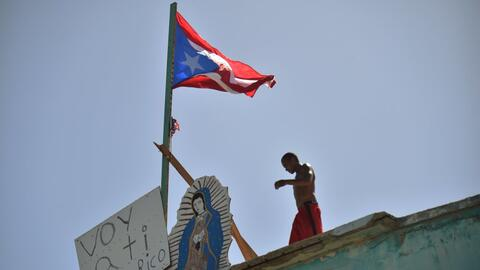 Javier, un vecino de Yabucoa, camina por el techo de su casa junto a una...