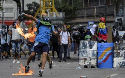 Un manifestante lanza una bomba casera a los cuerpos de seguridad que re...