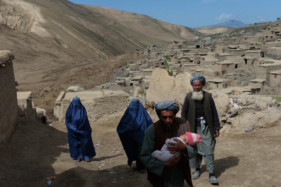 Afghan villagers walk near the scene in the landslide-hit Aab Bareek vil...