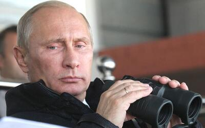 Russian premier Vladimir Putin uses binoculars to view presentations at...