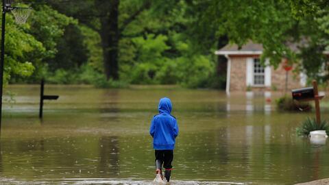 Un niño camina en un área inundada cercana a St. Louis, Mi...