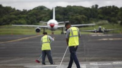 Trabajadores de limpieza limpian una zona de la pista de aterrizaje del...