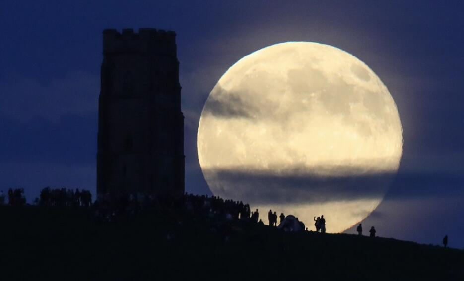 La luna llena se levanta tras Glastonbury, en Inglaterra, donde la gente...