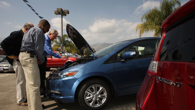 Un vendedor de autos Honda muestra un vehículo a potenciales clientes en...