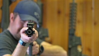 Un hombre prueba un rifle semi automático AR-15 en una armería de Oregón...
