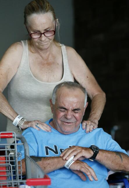 Sandra McKenna, rear, gives Segundo Garcia a massage as they spend their...