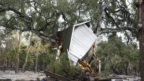 Una casa fue arrancada por el lodo y llegó hasta un árbol...